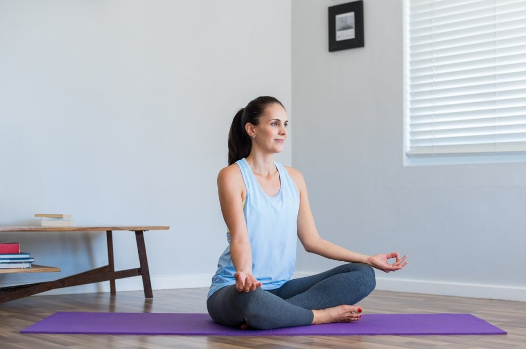 Mid adult woman sitting in lotus position on purple mat at home. Young serene woman feeling relaxed while meditating at home. Happy woman doing yoga and looking away.