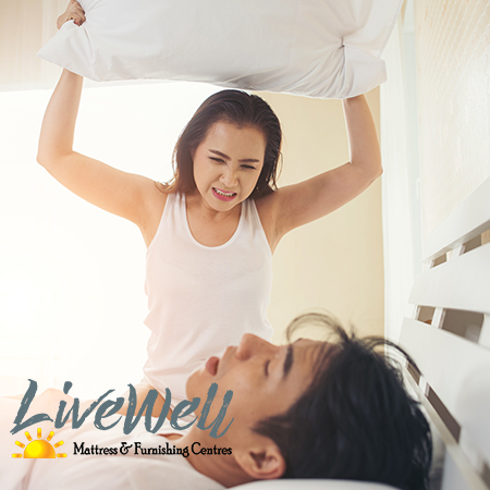 Lady with pillow over husbands head because he snores Live Well Mattress and Furnishing centres has adjustable bases to prevent snoring