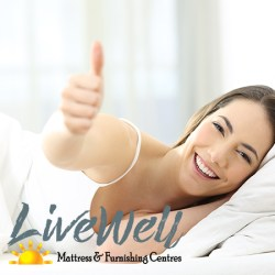 Woman in bed happy with mattress purchase at Live Well Mattress & Furnishing Centres