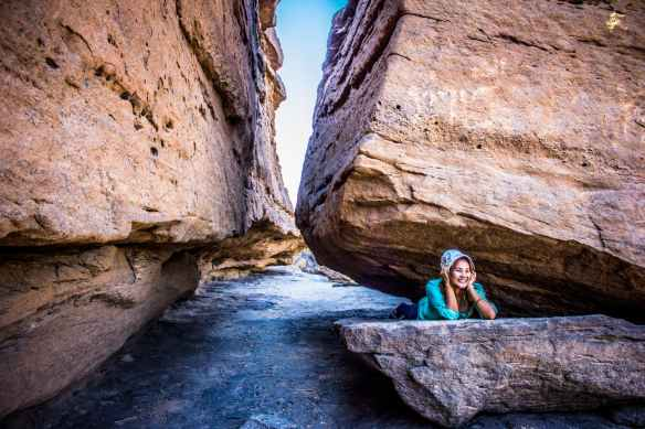 woman lying between rock formation at daytime