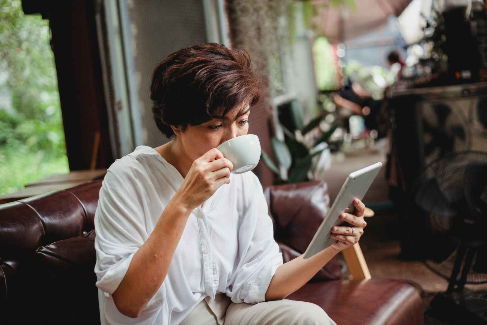 serious asian woman browsing tablet and drinking coffee