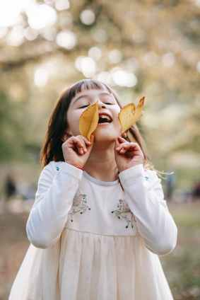 Joy with little girl with yellow leaves standing in autumn park