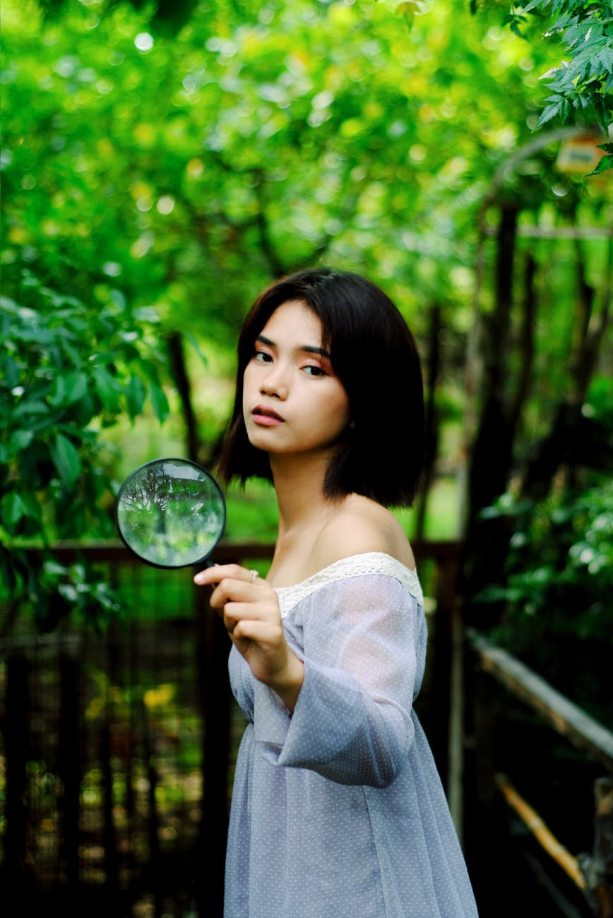 photo woman in white off shoulder dress holding magnifying glass