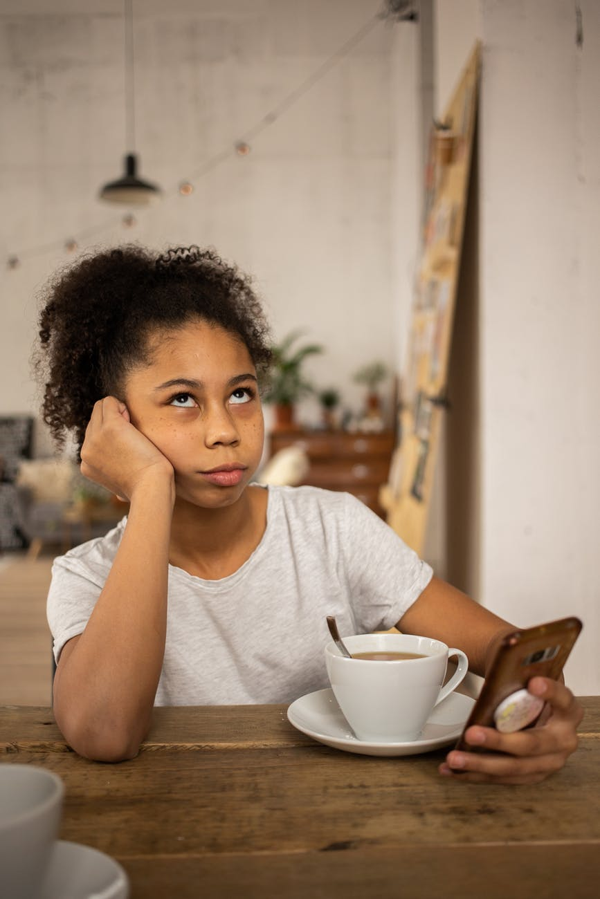 annoyed black girl surfing smartphone at table with coffee