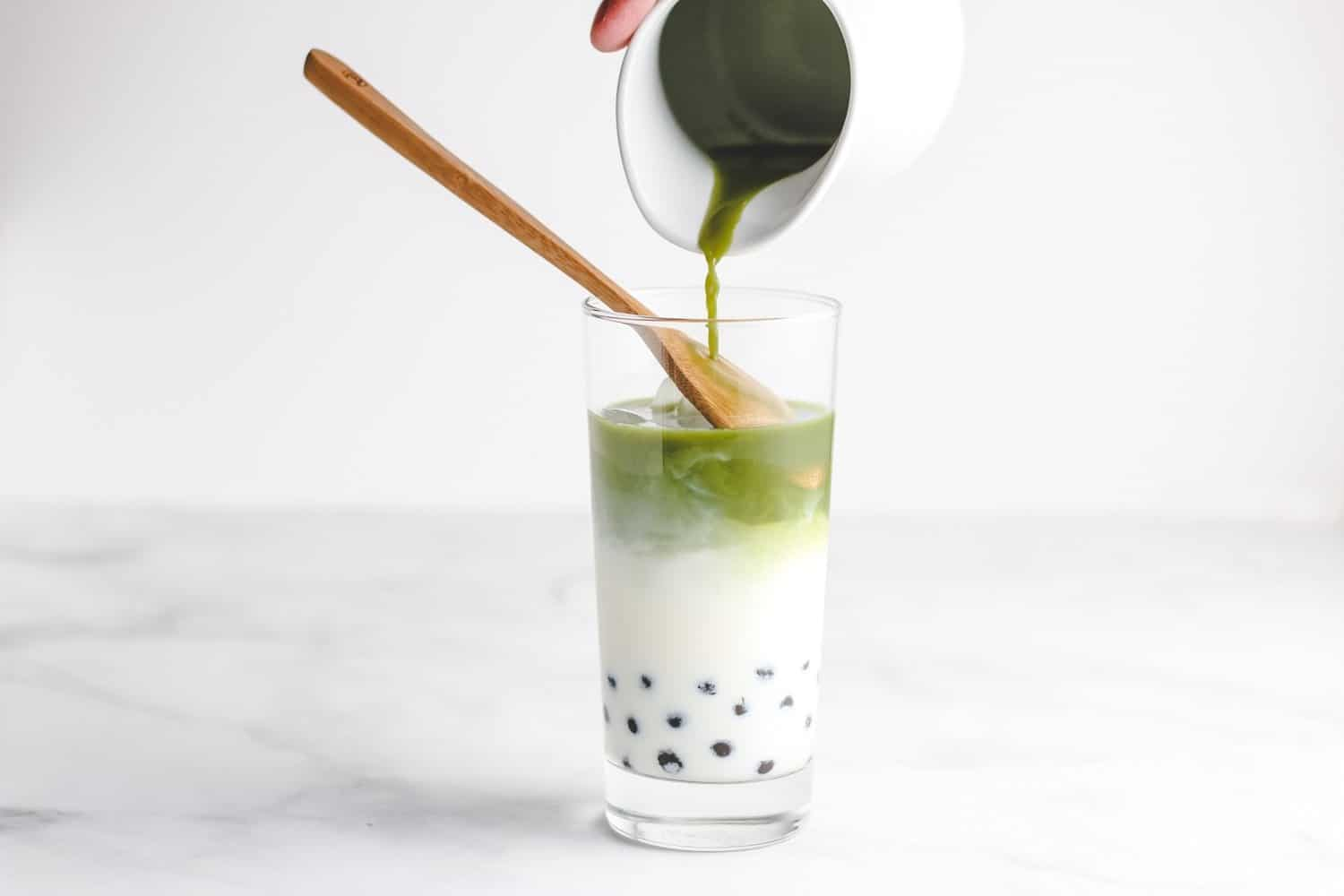 pour matcha tea layer over boba milk bubbles