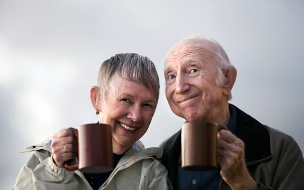 Photo image of man and woman approximately 70 years old smiling broadly holding coffee cups.