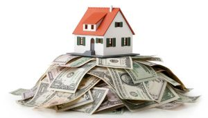 Image of a house sitting on top of a big pile of dollar bills.