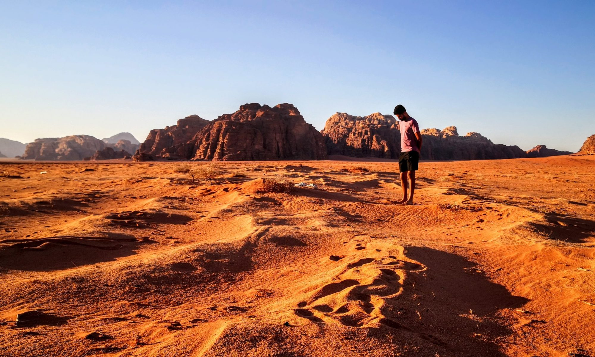 Person standing in the sand of Wadi Rum desert with rock formations in the back - one of the best spots in Jordan