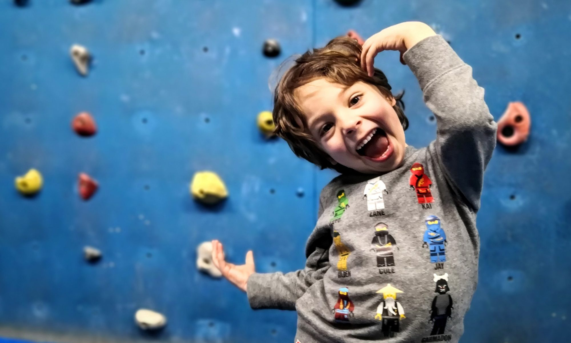 A happy child in front of a climbing wall at Climbat, Amman