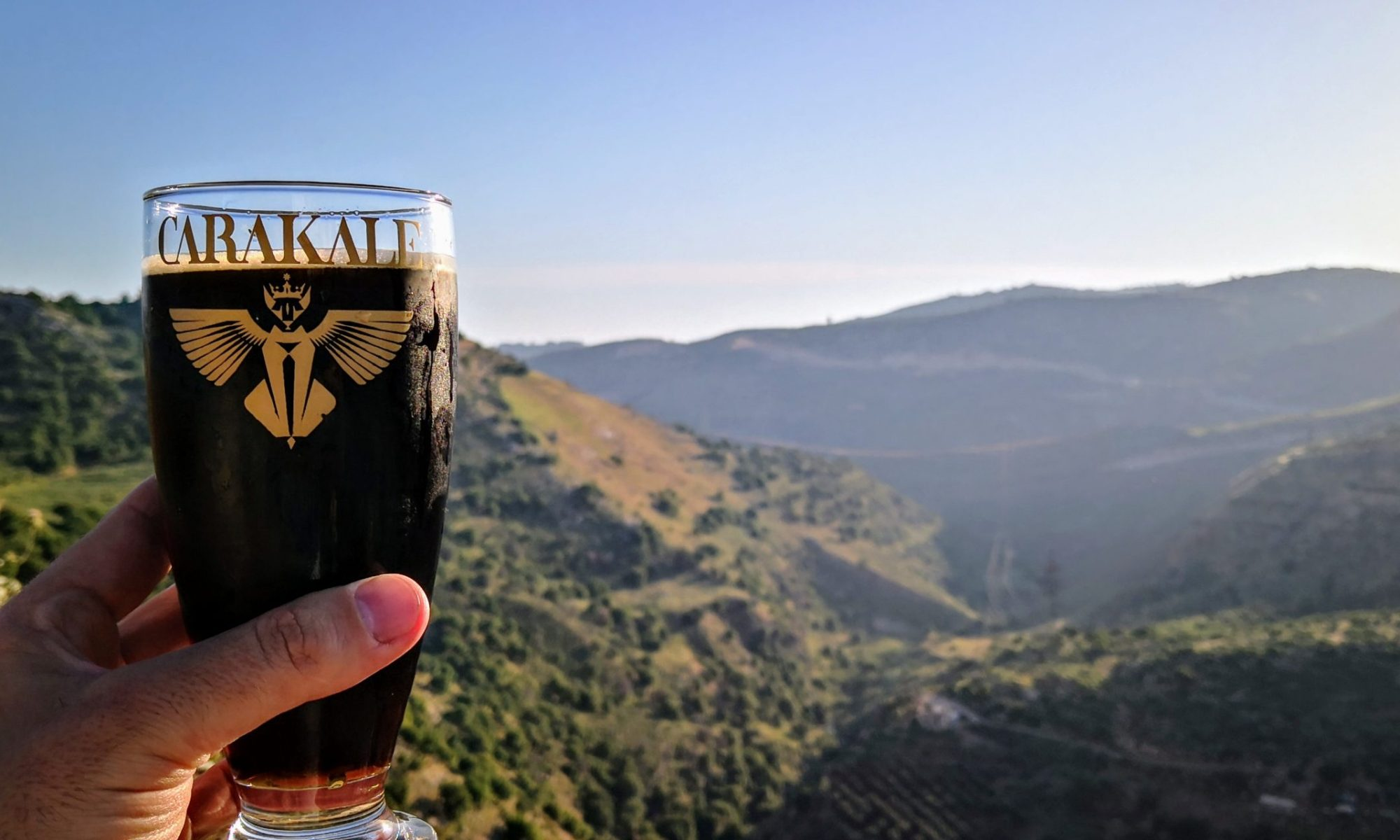 A glass of Schwarzbier in front of a canyon at Carakale Brewery located in Fuheis, Jordan