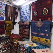 Many traditional colorful carpets with patterns hanged and alligned