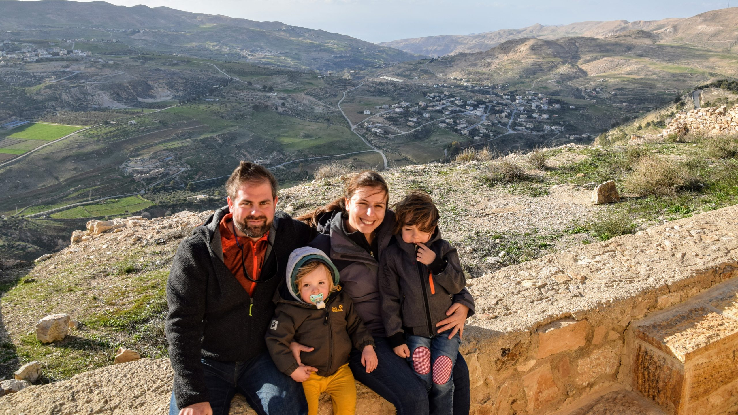 A Family sitting on the wall of ruins of the Karak Castle in Jordan