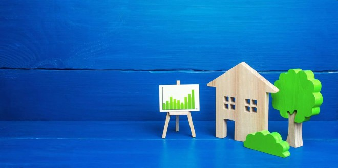 Residential building and easel with green positive upward trend chart
