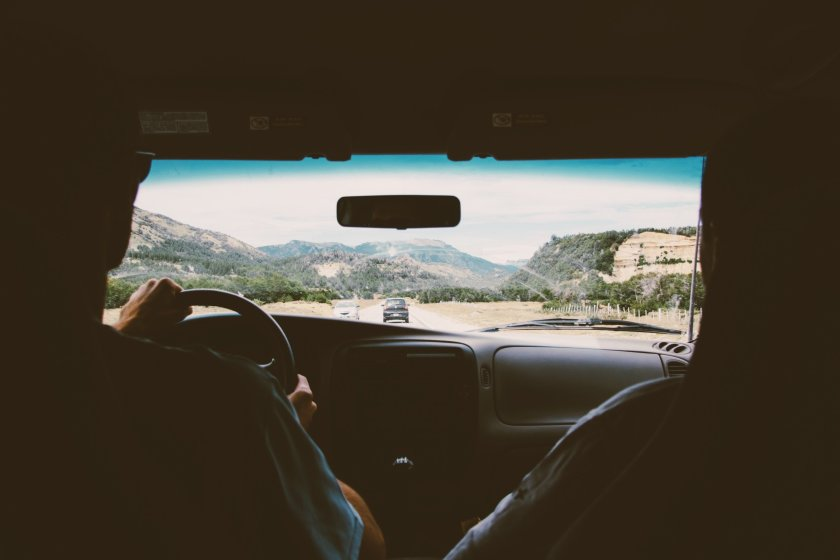 A photo taken from the inside of a car. Out of the windscreen there is a view of mountains.