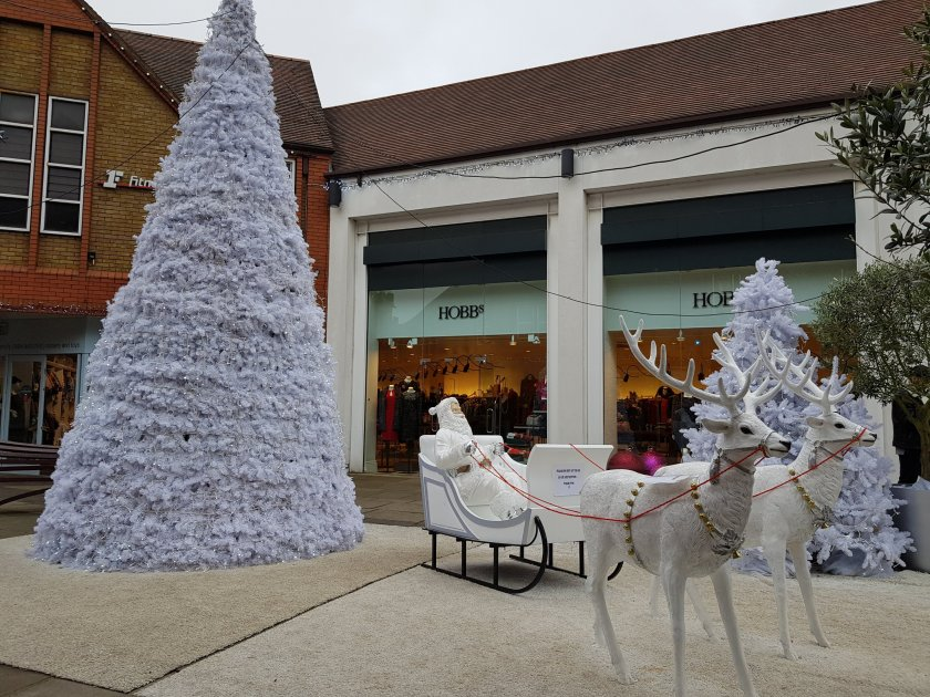 Santa in a sleigh with reindeer and christmas tree in Christopher Place festive display St Albans