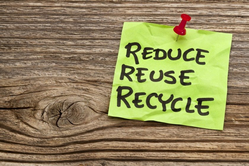 Sticky note saying reduce reuse recycle pinned to wooden board