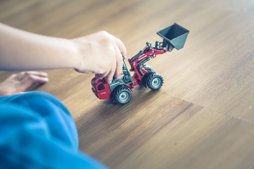 A child's hand driving a digger over a laminate floor.