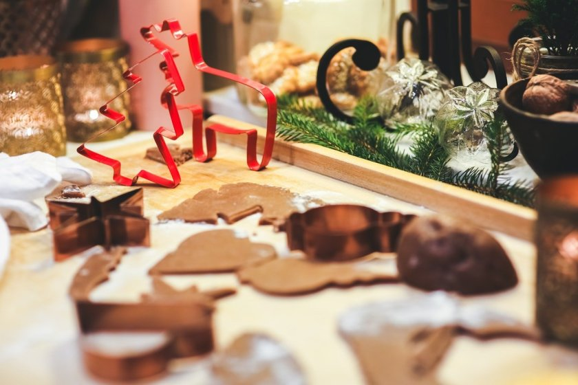 A picture of festive shaped cookie cutters and some baking. Winter decor in the background.