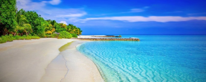 A picture of a stunning empty beach with clear water and blue skies.