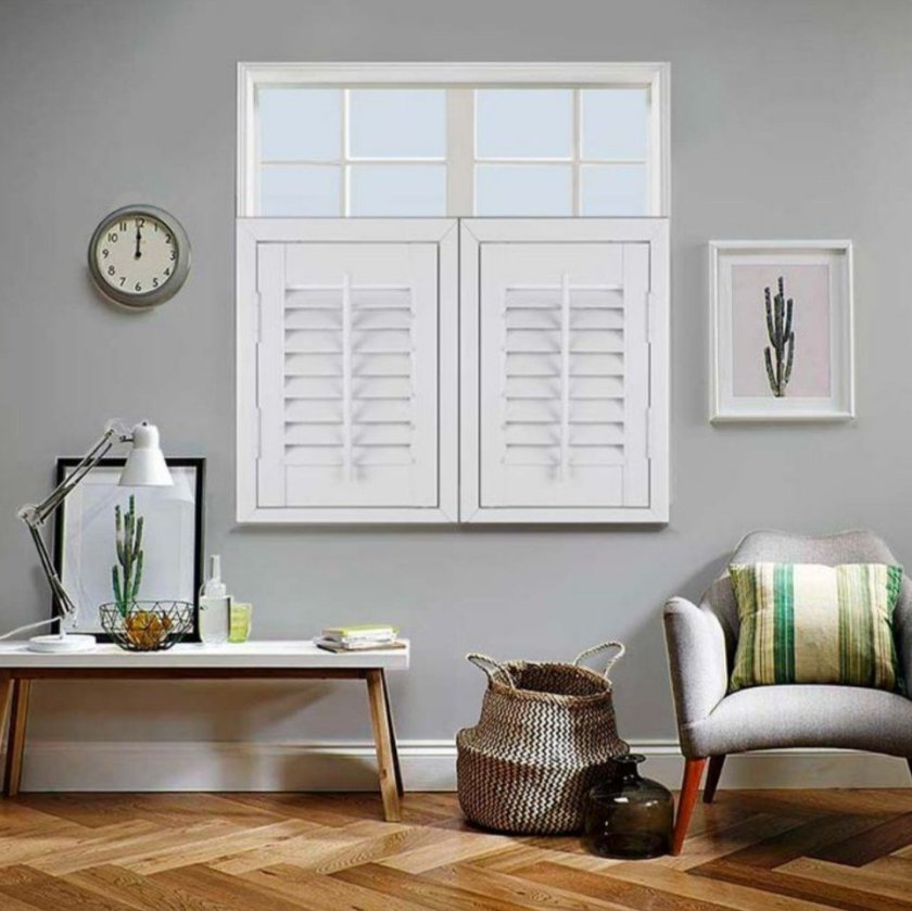 A picture of white wood cafe style shutters in a cosy living room.
