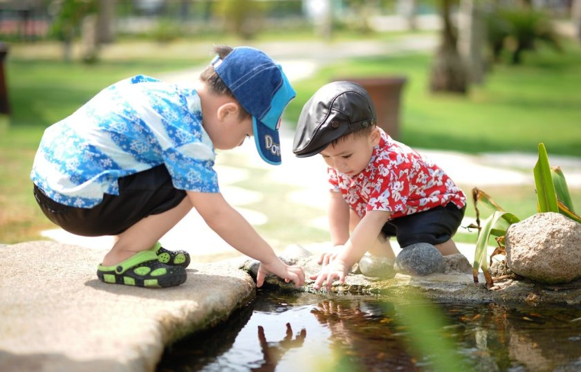 Image of two young children exploring a pond
