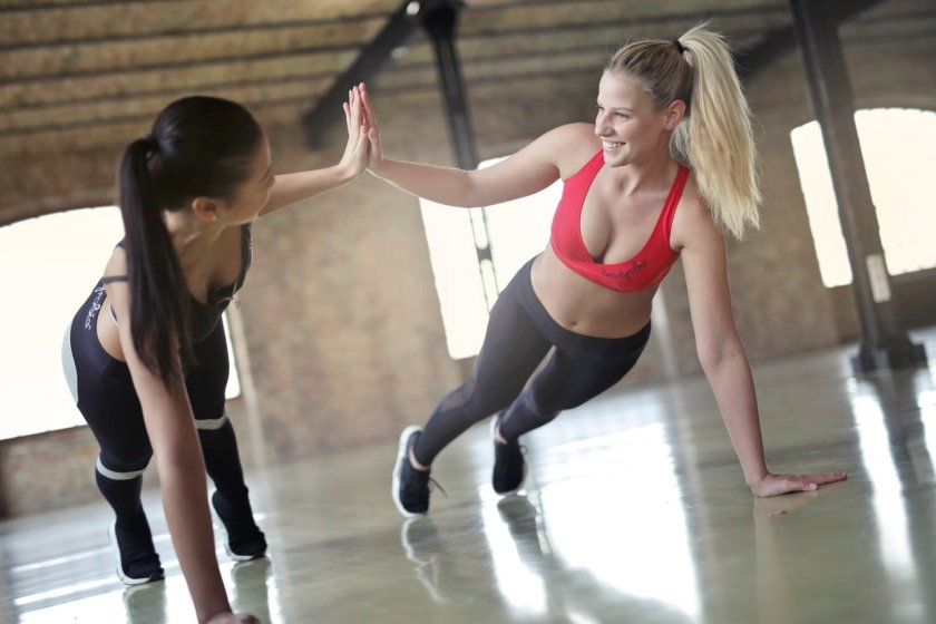 A photo of two women supporting each other while working out together. Women empowering each other.