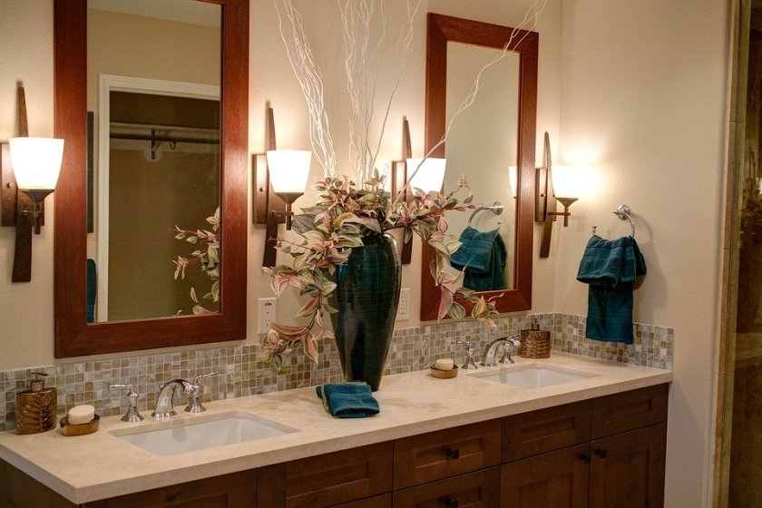 Double sink in bathroom. Large mirrors. Bathroom accessories. Large vase of flowers in centre