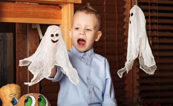 Halloween party with child holding toy ghost.