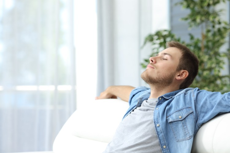 Being mindful - Is mindfulness for you? Image of young man relaxing on a sofa with his eyes closed
