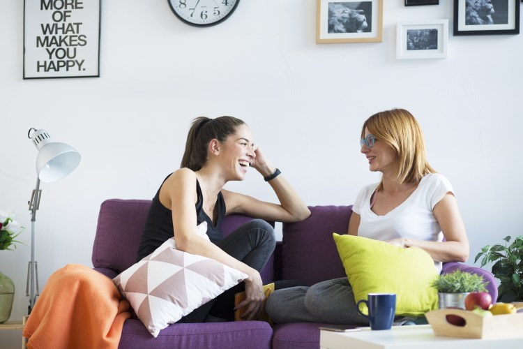 How to be more positive - Two happy young female friends conversing in the living room at home