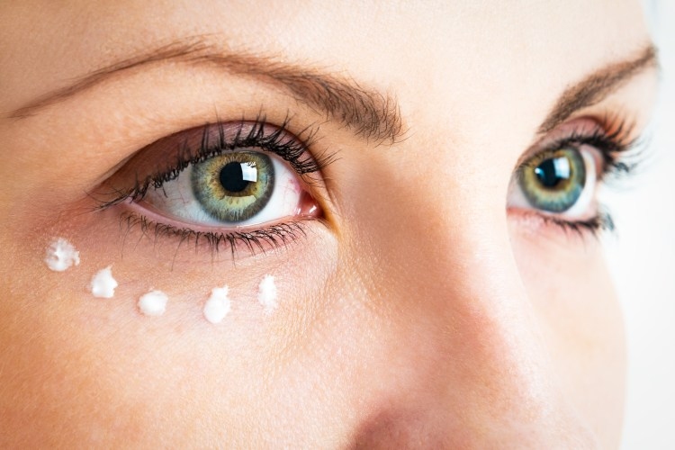 Do eye creams really work? Close up of woman's eye area with dots of eye cream underneath her right eye