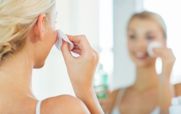 10 ways to slow signs of ageing around your eyes without using an eye cream. beauty, skin care and people concept - close up of smiling young woman cleaning her face with cotton disc and lotion at bathroom