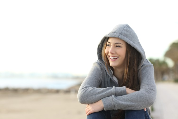 Confessions of a control freak: How to manage a fear of losing control. Portrait of a happy teenager girl smiling and looking at side outside on the beach