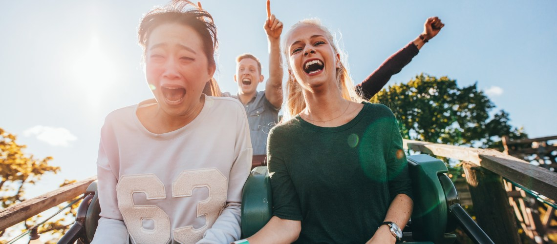 Confessions of a control-freak: How to manage a fear of losing control. Enthusiastic young friends riding amusement park ride