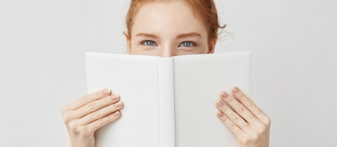 5 great books to help you lead a more positive lifestyle. Portrait of ginger girl hiding behind book looking at camera. Isolated on white background.