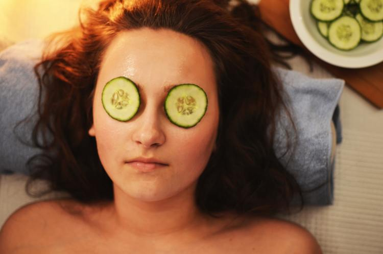 10 ways to slow signs of ageing around your eyes without using an eye cream. Image of woman lying down, relaxing with two cucumber slices over her eyes