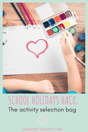 School holidays hack: The activity selection bag. Pinterest graphic displaying post title on a background image of child's arms and hands painting a picture of a red heart on a white piece of paper on a desk surrounded by paints and colouring pencils. livingprettyhappy.com