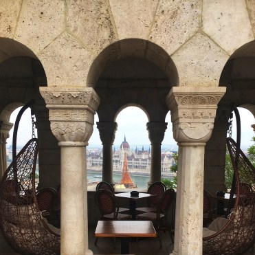 5 Things to do in Buda, Budapest. Image of view into cafe at Fisherman's Bastion with a through view of Pest and the Parliament building in the background