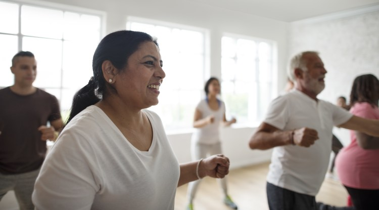 5 Ways exercise makes you happy.  Image of a diverse group of people taking part in an aerobic exercise class, smiling