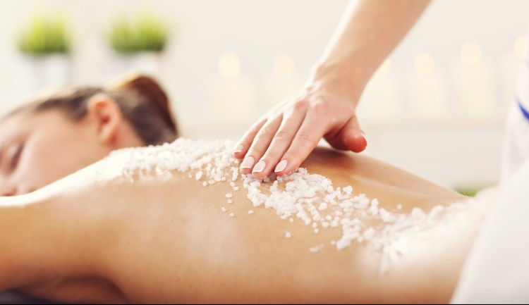 For the scrub of it: why should you exfoliate and how to do it right. Image of a woman getting an exfoliation treatment in the spa