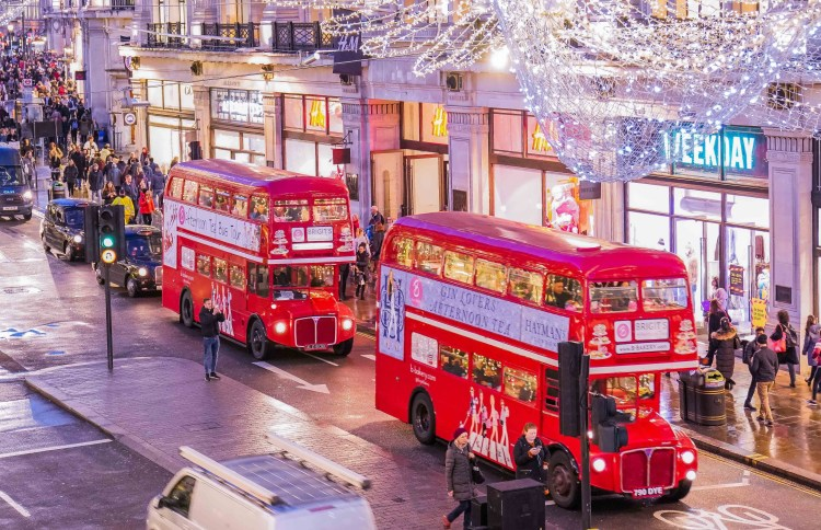 Happy Days: London Afternoon Tea Bus Tour. Image of Afternoon Tea Tour buses on a London high street with the Christmas lights above