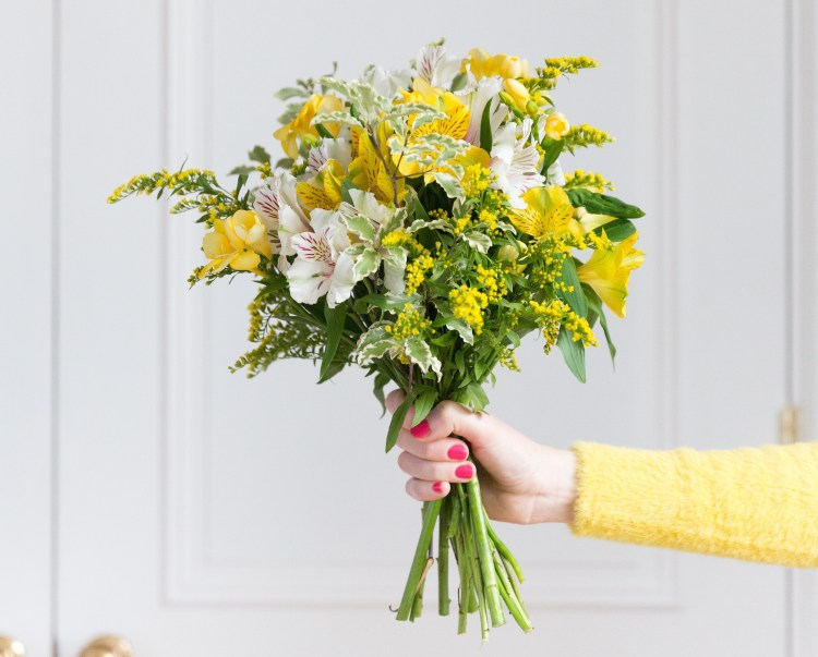 Blooming lovely: the positive power of flowers. Image of a female hand holding a yellow, white & green bouquet of flowers