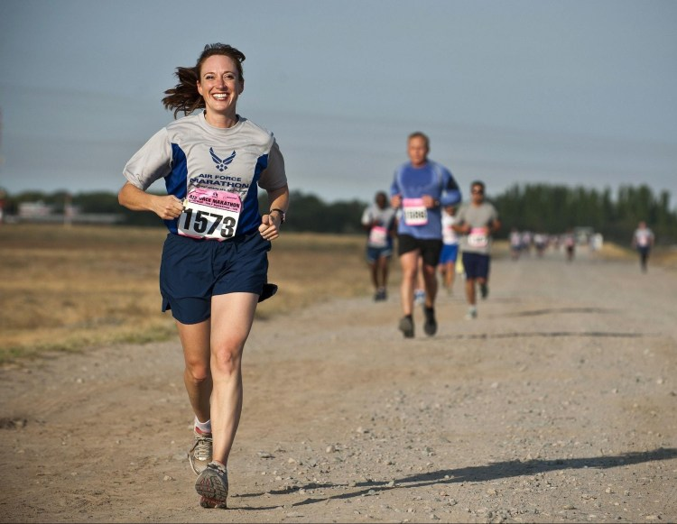 5 Ways exercise makes you happy.  Smiling woman competing in a marathon along a dirt track