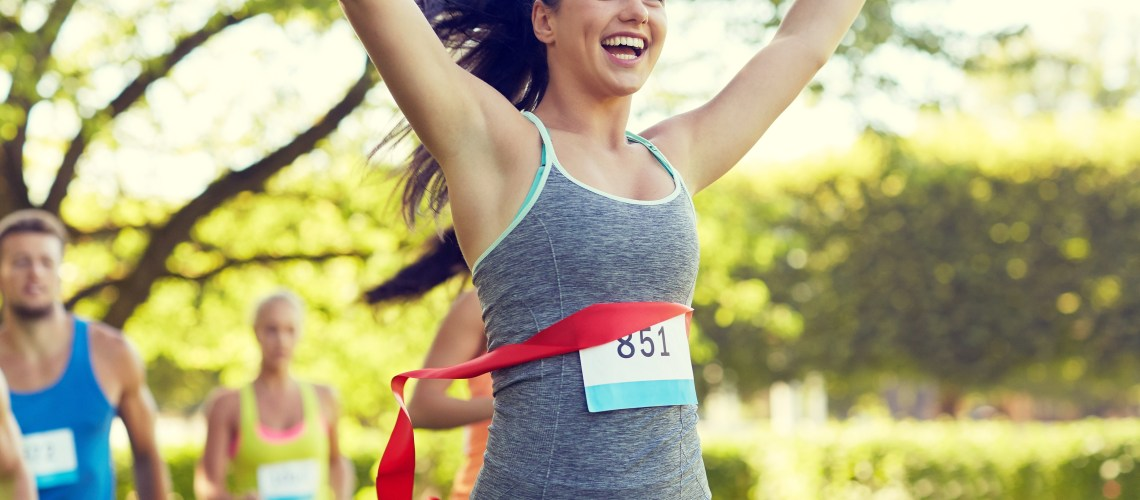 How to keep your running motivation. Image of happy woman winning race and coming first to finish red ribbon over group of sportsmen running marathon with badge numbers outdoors