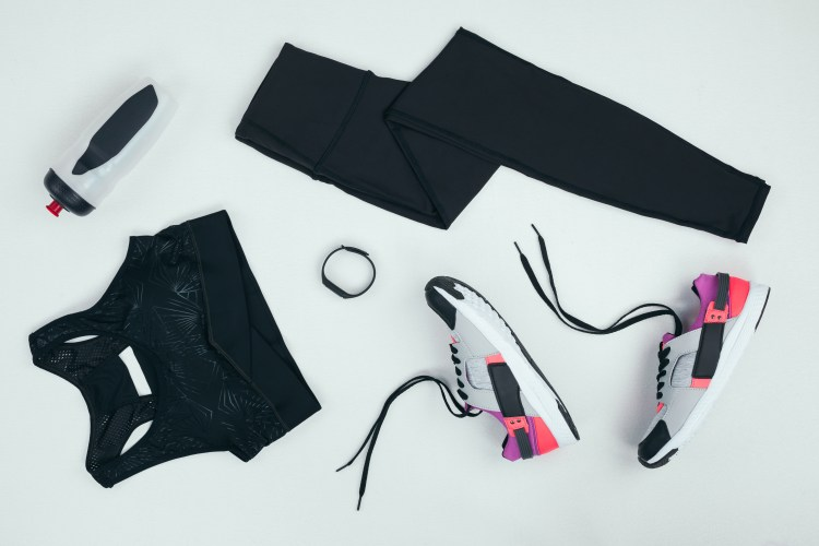 How to keep your running motivation. Image of  flat lay with sportswear with sneakers, fitness tracker and sports bottle isolated on grey.