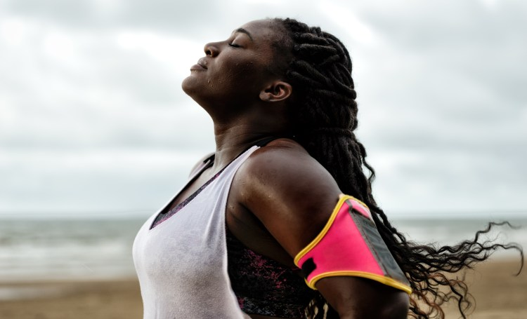 How to start running: tips for beginner runners. Image of woman standing with her eyes closed and head back breathing and regrouping after a run on the beach