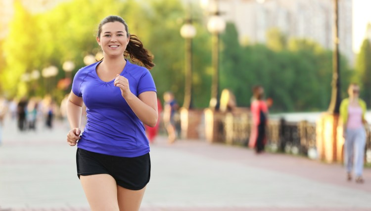 How to start running: tips for beginner runners. Young woman jogging and smiling in the street