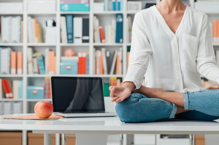 5 Useful ways mindfulness helps in your everyday life. Image of a Relaxed woman practicing meditation at home, she is sitting in the lotus position on the office desk, mindfulness concept
