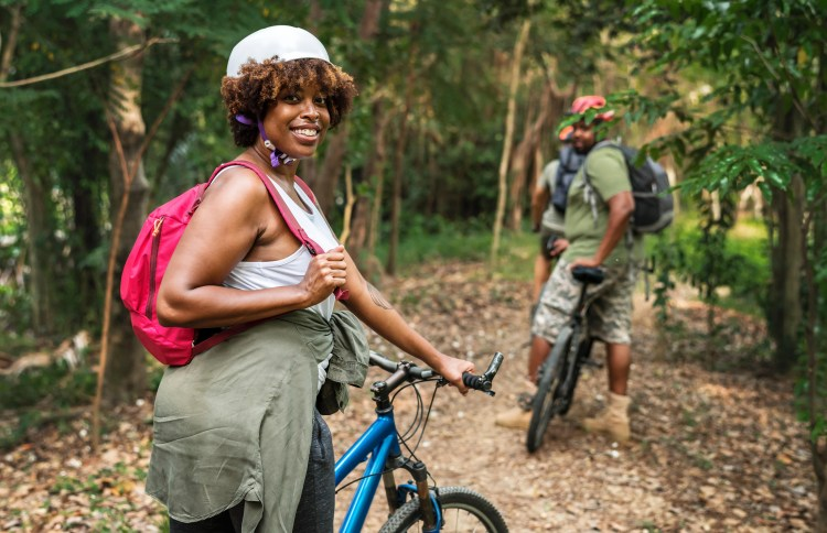 How to keep your running motivation.  How to stay motivated to run.  Image of a woman smiling ready to go on a bike ride in the woods with some companions