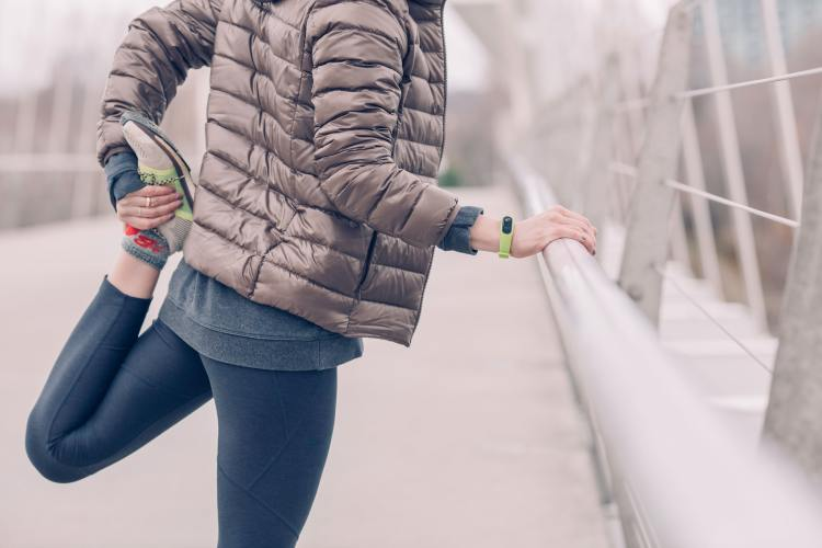 How to start running: tips for beginner runners. Image of woman stretching legs post jog